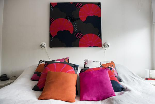 I Jonas och Heléns sovrum finns färgsprakande kuddar av både nyproducerat och loppisfyndat 1970-talstyg. Även tavlan på väggen är en textil.
