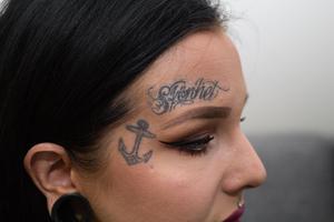 Hanna har fem tatueringar i ansiktet, bland annat orden Skönhet och Romantics. Här hittar vi också ett ankare och en rosett.
