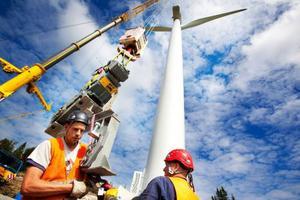 Alla verken kommer att vara kopplade till den nybyggda transformatorstationen i närheten. Den nymonterade vindsnurran sträcker sig 90 meter över marken. Två stora kranar behövs för att placera vingarna längst upp på pelarkroppen. Foto: Håkan Luthman