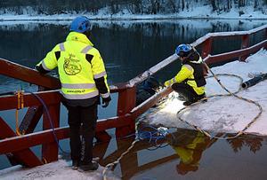 Tre personer från Svenska Tungdykargruppen vid en brodel som hamnat under vatten.