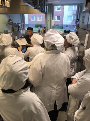 Kopplingen till att jobba ute i ett riktigt kök är viktig. Här besöker vi det stora produktionsköket på Torsberg som lagar väldigt stora mängder god mat.