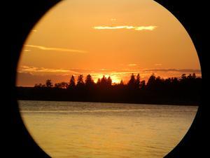 Solnedgång över Mälaren taget med en mobilkamera genom en kikare.