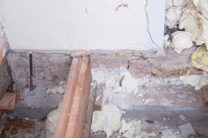 En sorts skum, som expanderar och snabbt stelnar, sprutades in under murstocken via borrade hål.