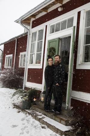 Stina och Thomas välkomnar in i det julpyntade skolhuset.