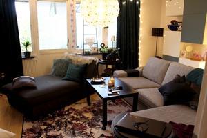 Rymligt vardagsrum med ljusslingor och divan.