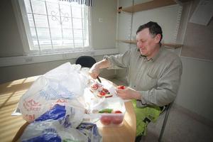 Adam Gericc skär rödlök och tomat. Det är rast i baracken på kraftverksbygget.