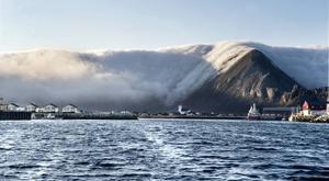 Dimman stoppas upp av fjällen på Väröy. Öster, norr och väster om ön ligger dimman tät på havet. I verkligheten ser det ut som ett gigantiskt vattenfall i ultrarapid som rör sig över bergstopparna men klarar inte av att når ner till havet på öns södra sida.