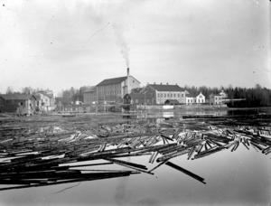 Timmerflottning med linspinneriet i Sörforsa som bakgrund.