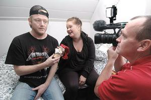 Kenta, Christer Johansson, kommer med en liten tomte i julklapp till flickvännen Vanessa, Martina Olsson. Peter Rox Eriksson låter filmkameran gå.