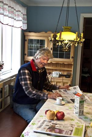 Radion står på i fönstret och Roland Olsson läser dagens tidning.