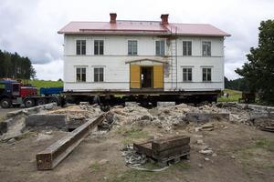 Huset har med hjälp av stålbalkar och hydraulik lyfts upp från stengrunden och upp på en flyttrailer.