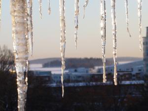 Vintervy över Mälaren sedd genom solbelysta istappar högt uppe i Punkts parkeringshus