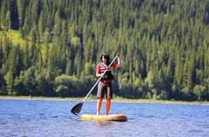 SUP, stand up paddleboard, är en ny aktivitet bland utbudet som besökare ägnar sig åt i Åre. Louise Ullerhed paddlar längs Åresjöns strand och ställer upp paddleboarden väl synligt på strategiska platser för att locka till sig turisternas nyfikenhet.