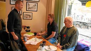 Göran Enander serverar påtår till Thomas Astvald och Göran Lennartsson, son och far.