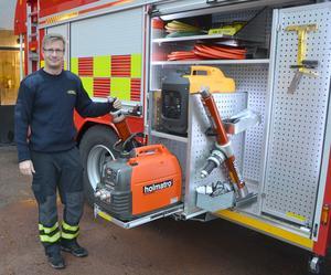 Thomas Eriksson visar den bärbara hydraulpump för klippverktyg som är en av nyheterna i den nya brandbilen.