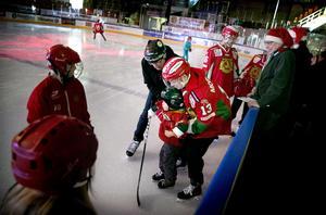 Emil Bejmo från Mora IK:S A-lag hjälper 4-åringa Levi Frost att stå på skridskorna.