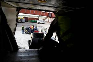 MARKSTRÖM. Direkt när planet landat är Tommy Strömberg framme och kopplar markström till planet. Det gör att kaptenen kan slå av motorerna.SLITIGT. Tommy Strömberg hivar ut väskor från planet, ett bökigt jobb i det trånga lastutrymmet. Kollegorna lyfter väskorna vidare till en transportvagn.