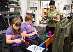 Uppdatering. Annika och Maria checkar in på Facebook innan träningspasset medan Kajsa går igenom övningarna.