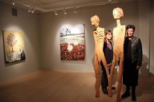 Inga Hjohlman och Torun Eliasson tittar fram bakom skulpturen Vi i utställningen på Bollnäs Konsthall. I bakgrunden syns Toruns målningar Uppdragen eka och Får.
