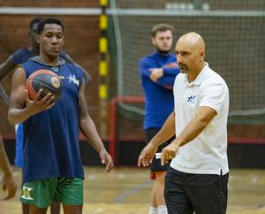 """Coachen Panagotis """"Jotti"""" Nikolaidis tränar sitt lag tufft och hårt men spelarna tycker att han är bra. CJ Jackson, som är en av de nya spelarna, lyssnar noga. Foto: Lennye Osbeck"""
