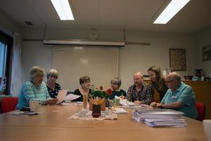 Gruppen ser över affischer som gjorts inför trivselträffar med jultema man anordnat i december.