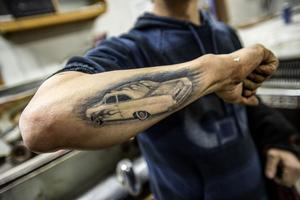 På armen är ett av de tidigare byggena förevigat som tatuering. En Opel Rekord från 1965.
