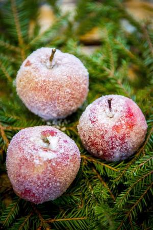Frostade äpplen. Du behöver: Några röda äpplen, äggvita och strösocker. Gör så här: Vispa äggvita lätt och doppa de röda äpplena i den. Rulla sedan äpplena i strösocker och pudra där det behövs. Lägg äpplena på lite granris för en effektfull dekoration på bordet.