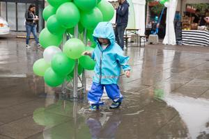 På Politikertorget gladdes en välklädd liten festivalbesökare åt vattenpölarna.