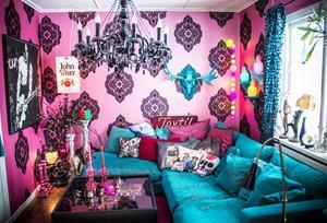 Vardagsrummet har rosa tapeter med svarta medaljonger. I ett litet rosa palats på golvet bor sköldpaddorna Elvis och Phil.