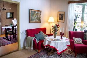 Vardagsrummet har originaltapeter och takmålningar bevarade från när huset byggdes 1941. Den röda soffgruppen är från samma tid.