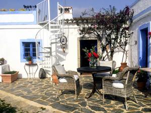 Det vitkalkade huset med blå knutar och dörrar är ett av flera gamla hustyper med en takterrass som tidigare har använts som torkställe för till exempel frukt. Foto: Maud Frykberg
