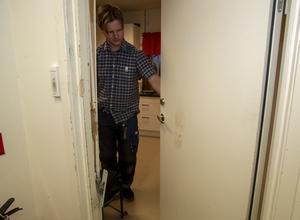 Simon Diamant som arbetar i butiken visar den förstörda dörren in till personalens lunchrum som har ett kraftigt skoavtryck efter att dörren sparkats in.