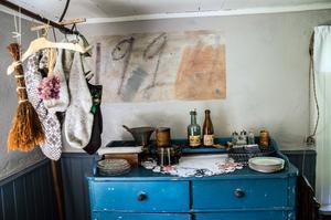 Stugan är inget museum, man ska kunna bo här, elda och diska. Ovanför farmors skänk har Maria skrapat fram gammalt klotter, kanske var det Dan Andersson som skrev 192?-någonting på väggen, antagligen 1920.