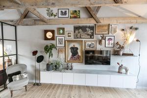 """Väggen i allrummet. Hatthållarna är ett loppisfynd i Skåne som Moa Kårebrand håller högt. Endast några få möbler är nyproducerade. De handlar mycket på loppis och gör om. """"Vi har inte så stor budget och vill återbruka"""", säger Olov Kårebrand."""