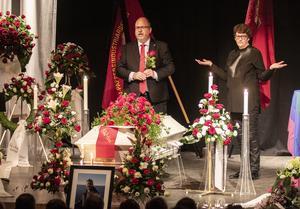 Längst fram på scenen stod den vita kistan, omgiven av mängder med blomsterarrangemang i rött och vitt. Vid kistan står officianten Karl Petter Thorwaldsson, och snett bakom honom Helle Klein.