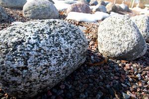 Under en sådan här sten ska Viktors aska sänkas ner. Skillnaden mellan askgravlunden och en vanlig minneslund är att här får varje person en egen sten. På stenen monteras en plakett med den avlidnes namn på.