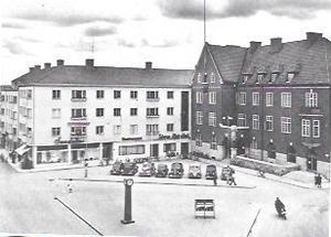 """En bild av torget med ingången till """"Storan"""" i hörnet av den vita byggnaden intill Sparbankshuset."""