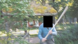 Här håller 77-åringen i den långa träkäppen som han slog sin granne med. Foto: Polisen
