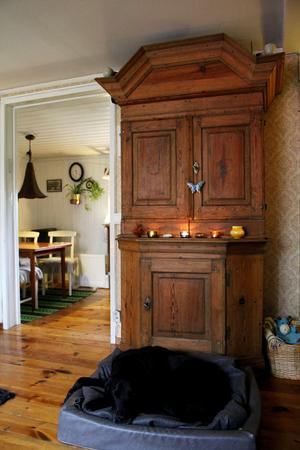 I vardagsrummet står bland annat ett stort vackert träskåp som Johan berättar är hans stil.