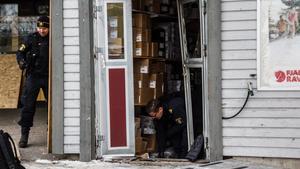 Polisens tekniker säkrade spår vid butikens dörr som blivit rammad.