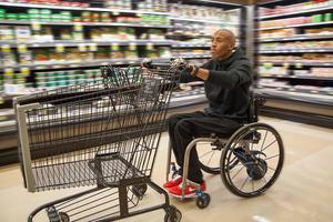 Påhängsmotorn Smart Drive  (extrahjulet där bak på rullstolen) hjälper inte bara de som har ont i axlarna, utan gör det också möjligt att använda båda armarna till annat. Bild: Permobil