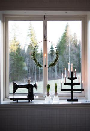 I matsalsfönstret står en svart symaskin av märket Husqvarna med sin vackra form.