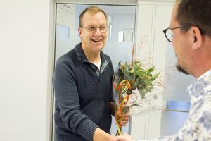 Nämndens ordförande Lars Andersson (L) lämnar över blommorna.