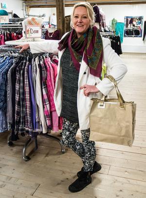 """""""Vi brukar ha långa köer utanför innan vi öppnar på onsdagar och lördagar. Vi har nog 5-600 kunder per dag"""" berättar Marianne Rådbo och mannekängar i lång jacka (150 kronor), stickad tröja (45 kronor), sjal (35 kronor) och en väska (50 kronor)."""