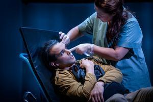 Jenny (Cicilia Sedvall) undersöker flyktingen Aziz (Othman Othman) som försökt ta livet av sig. Foto: Markus Gårder
