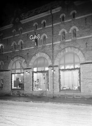 Pyntat i fönstren till Gasverkets kontor på Vasagatan 9. I fönstret till vänster fanns en kanna med ständigt rinnande mjölk ned i en grötkastrull. Foto: Eric Sjöqvist, Örebro. (Bildkälla: Örebro stadsarkiv)
