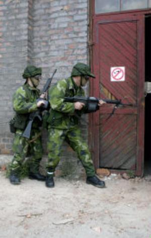 Två soldater gör sig redo att gå in i huset med fiender.