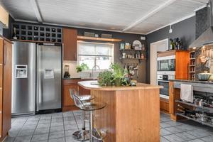 Köket, också med klinkergolv är inrett i gråare färger – med detaljer i oljad ek.