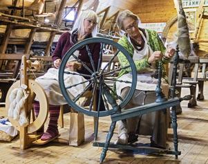 Elisabeth Jacobs spinner tretrådigt ullgarn av jämtlandsfårull. Bredvid henne spinner Inga-Lena Åkesson lintråd.