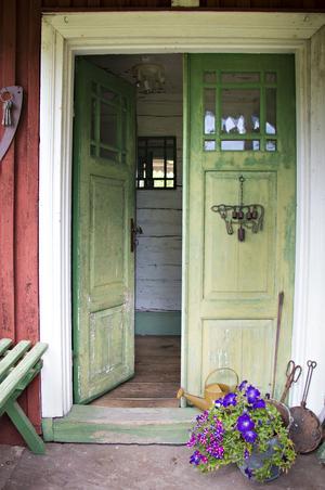 Den gröna gamla pardörren välkomnar in till torpet som från början var hem åt soldaten Palm och hans familj. De har också fått ge namn åt plats – Palmasbo